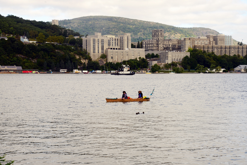Members of the Sea Change Flotilla in a paper boat on the Hudson river in front of West Point Military Academy. Photo by Ellen Davidson.